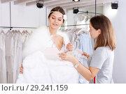 Купить «Consultant helping woman with fitting of white gown», фото № 29241159, снято 17 сентября 2018 г. (c) Яков Филимонов / Фотобанк Лори