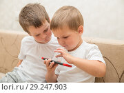 Купить «Two boys playing games on smartphone at home», фото № 29247903, снято 29 августа 2018 г. (c) Юлия Бабкина / Фотобанк Лори