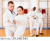 Купить «Woman fencer practicing new movements with trainer at fencing room», фото № 29248543, снято 11 июля 2018 г. (c) Яков Филимонов / Фотобанк Лори