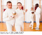Купить «Girl fencer exercising new techniques with trainer indoors», фото № 29248547, снято 11 июля 2018 г. (c) Яков Филимонов / Фотобанк Лори