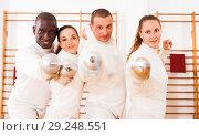 Купить «Smiling fencers posing with foils together at fencing room», фото № 29248551, снято 11 июля 2018 г. (c) Яков Филимонов / Фотобанк Лори