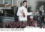 Купить «Happy male holding newly produced bottle of wine», фото № 29256875, снято 21 сентября 2016 г. (c) Яков Филимонов / Фотобанк Лори