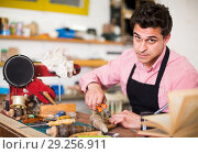 Купить «Craftsman in uniform working in carpentry», фото № 29256911, снято 8 апреля 2017 г. (c) Яков Филимонов / Фотобанк Лори