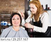 Купить «Young hairdresser working in salon», фото № 29257167, снято 7 марта 2017 г. (c) Яков Филимонов / Фотобанк Лори