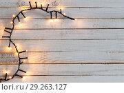 Купить «Christmas lights on white wooden background», фото № 29263127, снято 15 октября 2018 г. (c) Майя Крученкова / Фотобанк Лори