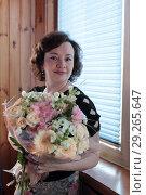 Купить «Женщина средних лет с букетом цветов», эксклюзивное фото № 29265647, снято 16 июля 2017 г. (c) Дмитрий Неумоин / Фотобанк Лори