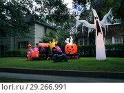 Купить «The house is decorated for Halloween: Inflatable train with the dead, big pumpkin, black cat huge and small ghost. Night, Houston, Texas, United States», фото № 29266991, снято 18 октября 2018 г. (c) Ирина Кожемякина / Фотобанк Лори