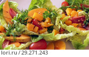 Купить «Colorful salad with baked pumpkin. Recipe: lettuce leaves, pieces of pumpkin, chopped cherry tomatoes and», видеоролик № 29271243, снято 27 августа 2018 г. (c) Яков Филимонов / Фотобанк Лори