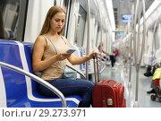 Купить «Woman using phone inside subway», фото № 29273971, снято 19 сентября 2018 г. (c) Яков Филимонов / Фотобанк Лори