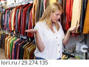 Купить «Displeased woman choosing leather clothes», фото № 29274135, снято 5 сентября 2018 г. (c) Яков Филимонов / Фотобанк Лори