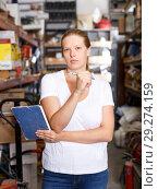 Купить «Young woman standing near racks in build store bebore buying tools», фото № 29274159, снято 20 сентября 2018 г. (c) Яков Филимонов / Фотобанк Лори
