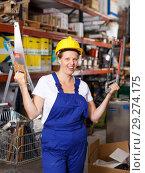 Купить «Young female in uniform and helmet holding saw near shelves with tools», фото № 29274175, снято 20 сентября 2018 г. (c) Яков Филимонов / Фотобанк Лори