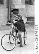 Купить «Старинный портрет трехлетней девочки, которая впервые в жизни пытается сесть на трехколесный велосипед. 1958», эксклюзивное фото № 29274631, снято 23 января 2019 г. (c) Валерия Попова / Фотобанк Лори