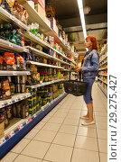 Женщина выбирает кофе в супермаркете Hit Ullrich Consumer market, Берлин, Германия (2018 год). Редакционное фото, фотограф Ольга Коцюба / Фотобанк Лори