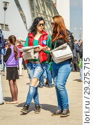 Купить «Russia, Samara, April 12, 2016: young beautiful girls give out a free newspaper about the first flight of Yuri Gagarin to space, on a holiday, Cosmonautics Day, on a square with a space rocket, on a spring sunny day.», фото № 29275715, снято 12 апреля 2016 г. (c) Акиньшин Владимир / Фотобанк Лори
