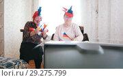 Купить «Two elderly women watching TV in russian accessories and happily waving Russian flags», видеоролик № 29275799, снято 23 января 2019 г. (c) Константин Шишкин / Фотобанк Лори