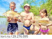 Купить «Daddy son and daughter holding caught fish in the hot summer on the banks of the river.», фото № 29276095, снято 1 июля 2018 г. (c) Акиньшин Владимир / Фотобанк Лори