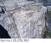 Купить «Flat rock Preikestolen over fjord Lysefjorden is natural attraction. Top view and flight down above cliff. Preacher's Pulpit or Preacher's Chair is in Forsand in Rogaland, Norway», фото № 29276383, снято 4 июля 2018 г. (c) Кекяляйнен Андрей / Фотобанк Лори