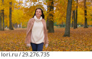 Купить «happy young woman walking in autumn park», видеоролик № 29276735, снято 18 октября 2018 г. (c) Syda Productions / Фотобанк Лори