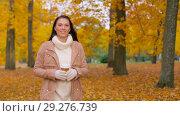 Купить «woman drinking takeaway coffee in autumn park», видеоролик № 29276739, снято 18 октября 2018 г. (c) Syda Productions / Фотобанк Лори