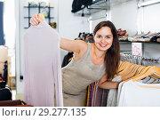 Купить «Woman choosing new long sleeve blouse», фото № 29277135, снято 26 сентября 2016 г. (c) Яков Филимонов / Фотобанк Лори