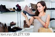 Купить «Young woman choosing fall boots in shoes store», фото № 29277139, снято 26 сентября 2016 г. (c) Яков Филимонов / Фотобанк Лори