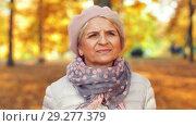 Купить «happy senior woman walking along autumn park», видеоролик № 29277379, снято 22 октября 2018 г. (c) Syda Productions / Фотобанк Лори