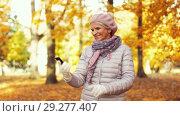 Купить «senior woman taking selfie at autumn park», видеоролик № 29277407, снято 22 октября 2018 г. (c) Syda Productions / Фотобанк Лори