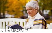 Купить «happy senior woman reading book at autumn park», видеоролик № 29277447, снято 22 октября 2018 г. (c) Syda Productions / Фотобанк Лори