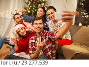 Купить «friends celebrating christmas and taking selfie», фото № 29277539, снято 17 декабря 2017 г. (c) Syda Productions / Фотобанк Лори