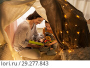 Купить «happy family reading book in kids tent at home», фото № 29277843, снято 27 января 2018 г. (c) Syda Productions / Фотобанк Лори