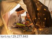 Купить «happy family reading book in kids tent at home», фото № 29277843, снято 27 января 2018 г. (c) Syda Productions / Фотобанк Лори