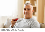 Купить «man drinking red wine from glass at home», фото № 29277939, снято 14 апреля 2018 г. (c) Syda Productions / Фотобанк Лори