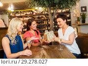 Купить «women giving present to friend at wine bar», фото № 29278027, снято 25 июня 2018 г. (c) Syda Productions / Фотобанк Лори