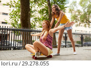 Купить «teenage girls riding skateboard on city street», фото № 29278055, снято 19 июля 2018 г. (c) Syda Productions / Фотобанк Лори