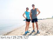 Купить «happy couple in sports clothes and shades on beach», фото № 29278127, снято 1 августа 2018 г. (c) Syda Productions / Фотобанк Лори