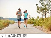 Купить «couple in sports clothes running along beach path», фото № 29278151, снято 1 августа 2018 г. (c) Syda Productions / Фотобанк Лори