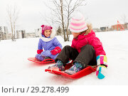 happy little girls on sleds outdoors in winter. Стоковое фото, фотограф Syda Productions / Фотобанк Лори