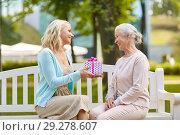 Купить «daughter giving present to senior mother at park», фото № 29278607, снято 11 августа 2017 г. (c) Syda Productions / Фотобанк Лори