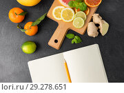 Купить «close up of fruits and notebook on slate table top», фото № 29278651, снято 4 апреля 2018 г. (c) Syda Productions / Фотобанк Лори