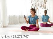Купить «woman with smartphone at yoga studio», фото № 29278747, снято 21 июня 2018 г. (c) Syda Productions / Фотобанк Лори
