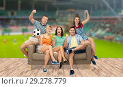 Купить «friends or football fans with soccer ball on sofa», фото № 29278779, снято 30 июня 2018 г. (c) Syda Productions / Фотобанк Лори