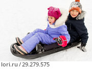 Купить «little kids sliding on sled down hill in winter», фото № 29279575, снято 10 февраля 2018 г. (c) Syda Productions / Фотобанк Лори