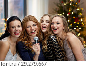 Купить «happy young women with microphone singing karaoke», фото № 29279667, снято 21 ноября 2015 г. (c) Syda Productions / Фотобанк Лори