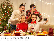 Купить «friends taking selfie at christmas dinner», фото № 29279743, снято 17 декабря 2017 г. (c) Syda Productions / Фотобанк Лори