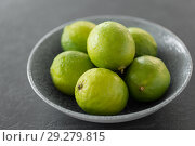 Купить «close up of whole limes in bowl on slate table top», фото № 29279815, снято 4 апреля 2018 г. (c) Syda Productions / Фотобанк Лори