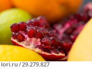 Купить «close up of pomegranate on stone table», фото № 29279827, снято 4 апреля 2018 г. (c) Syda Productions / Фотобанк Лори