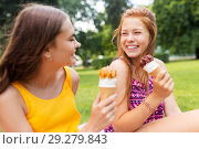 Купить «teenage girls eating ice cream at picnic in park», фото № 29279843, снято 19 июля 2018 г. (c) Syda Productions / Фотобанк Лори