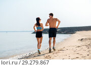 Купить «couple in sports clothes running along on beach», фото № 29279867, снято 1 августа 2018 г. (c) Syda Productions / Фотобанк Лори