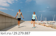 Купить «happy couple warming up on pier before training», фото № 29279887, снято 1 августа 2018 г. (c) Syda Productions / Фотобанк Лори